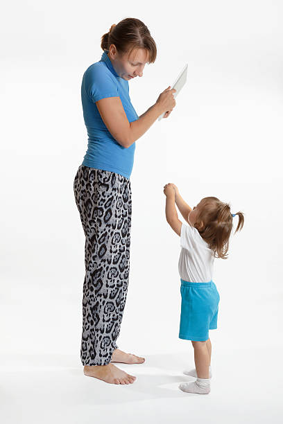 Little girl is begging her mother for a tablet pad stock photo