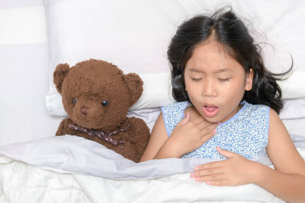 Little girl is coughing and sore throat stock photo