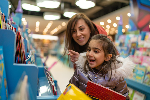 Little girl is delighted when her mother shows where the book her daughter wants in the bookstore