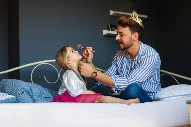 La niñita está haciendo lo que su padre - foto de stock