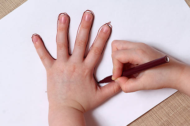 Little girl is drawing contour of the hand. stock photo