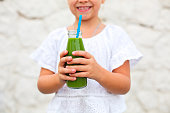 Little girl is drinking green fresh juice using straw outdoors. Close up