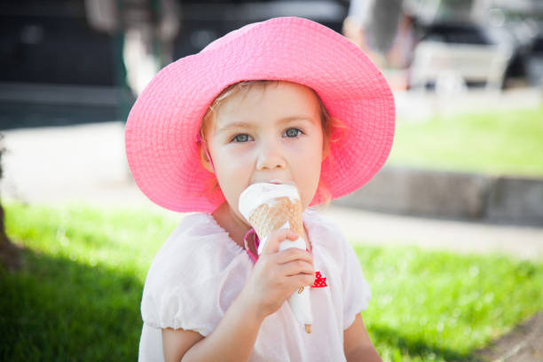 Little girl is enjoying and holding melting ice cream in cones in her hands. Child is eating gelato in resort outdoors in town streets. Kid is in pink hat. Concept of childhood, summer, traveling. stock photo