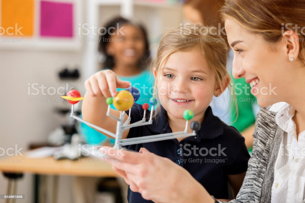 Little girl is excited to learn about the solar system stock photo