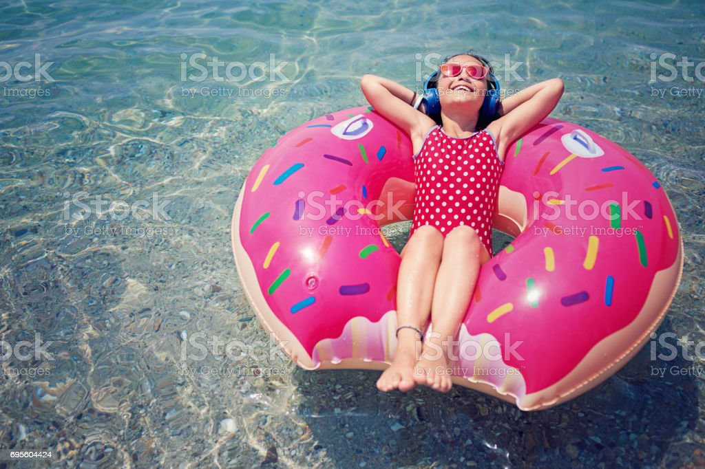 Little girl is floating in the water and listening the music stock photo