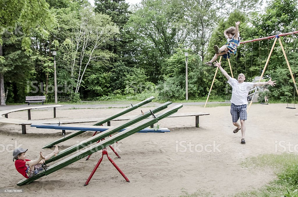 Little girl is flying after brother swings her in air royalty-free stock photo