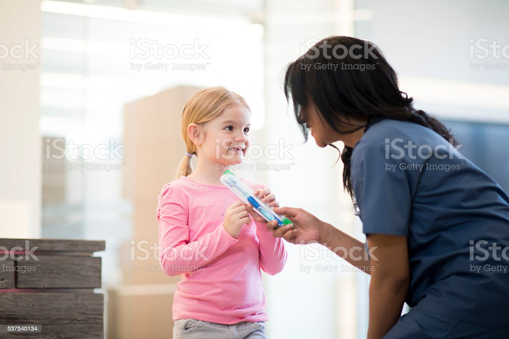 A little girl is getting a new tooth brush at her stock photo