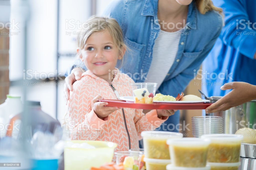 Happy Caucasian girl smiles as she receives a tray of healthy food...