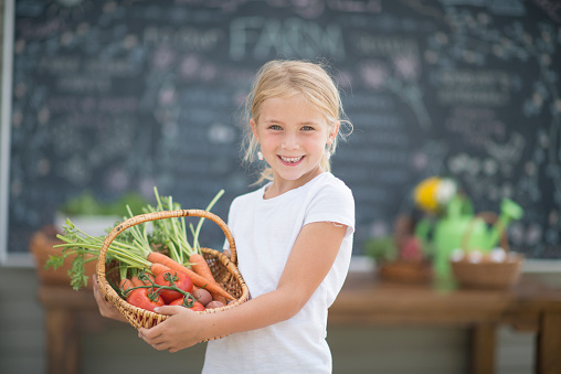 A little girl is holding a basket of fresh vegetables