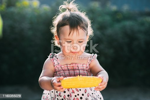 istock A little girl is holding boiled corn and thinking whether to eat or not 1160055029