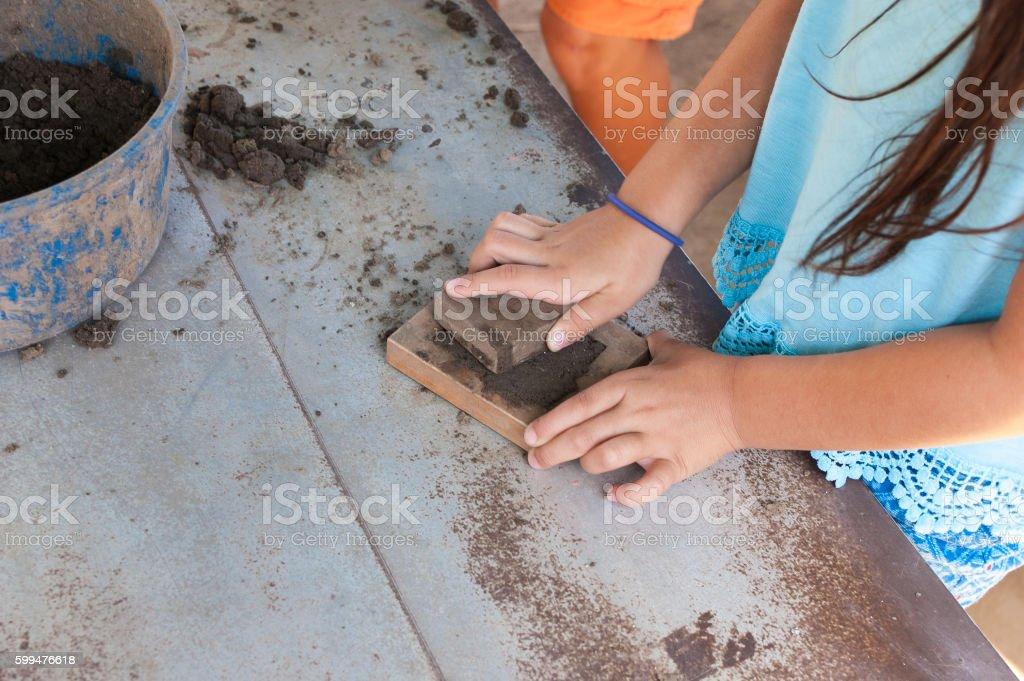 Little girl is learning how to make adobe bricks stock photo