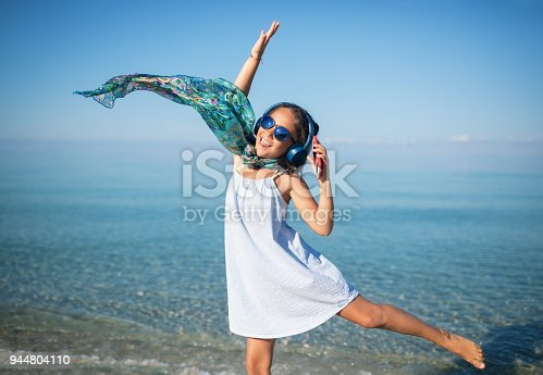 istock Little girl is listening the music and dancing on the beach 944804110