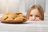 istock Little girl is looking on delicious cookies and looks hungry. 936548908