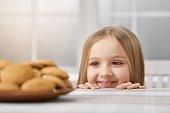 istock Little girl is looking on delicious cookies. 944271200