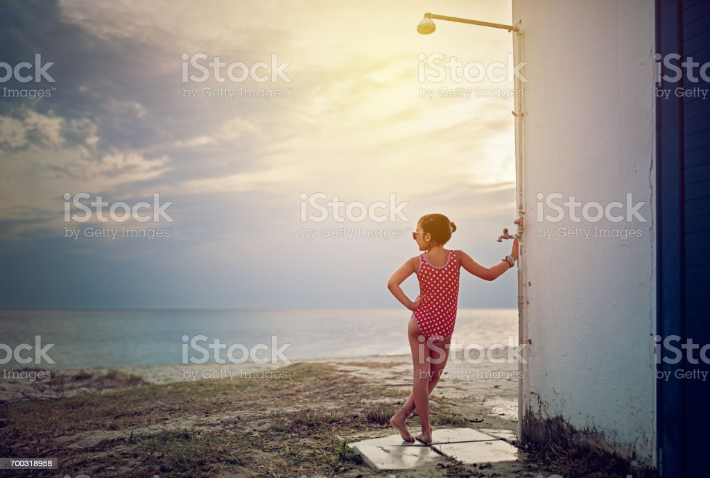 Little girl is looking sad the ocean at the last day of her vacation stock photo