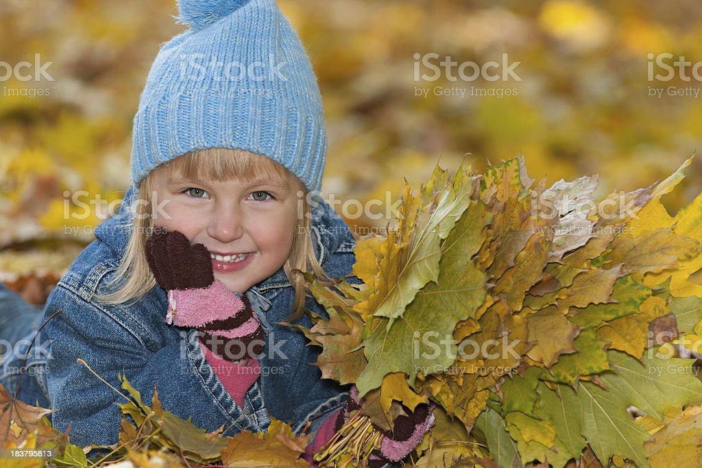Little girl is lying on the yellow leaves royalty-free stock photo