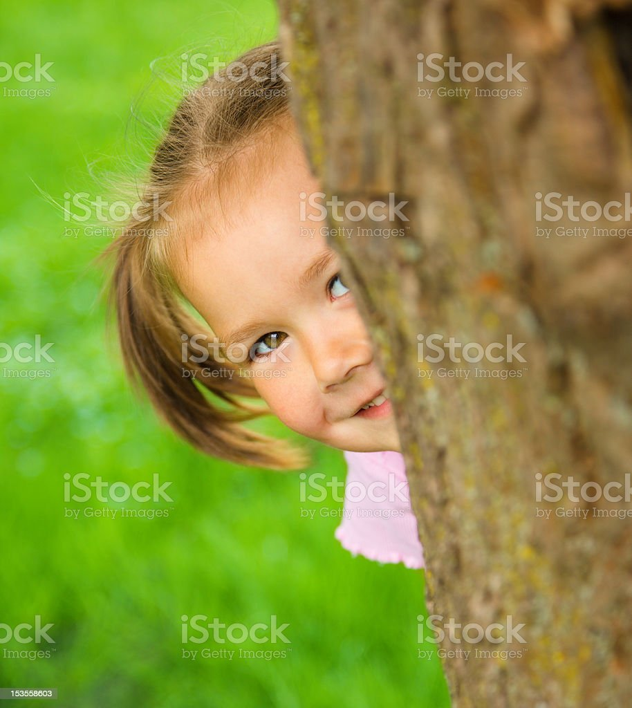 Little girl is playing hide and seek outdoors royalty-free stock photo