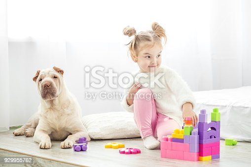 istock Little girl is playing toys. Child in sweater and pink pants. Th 929955762