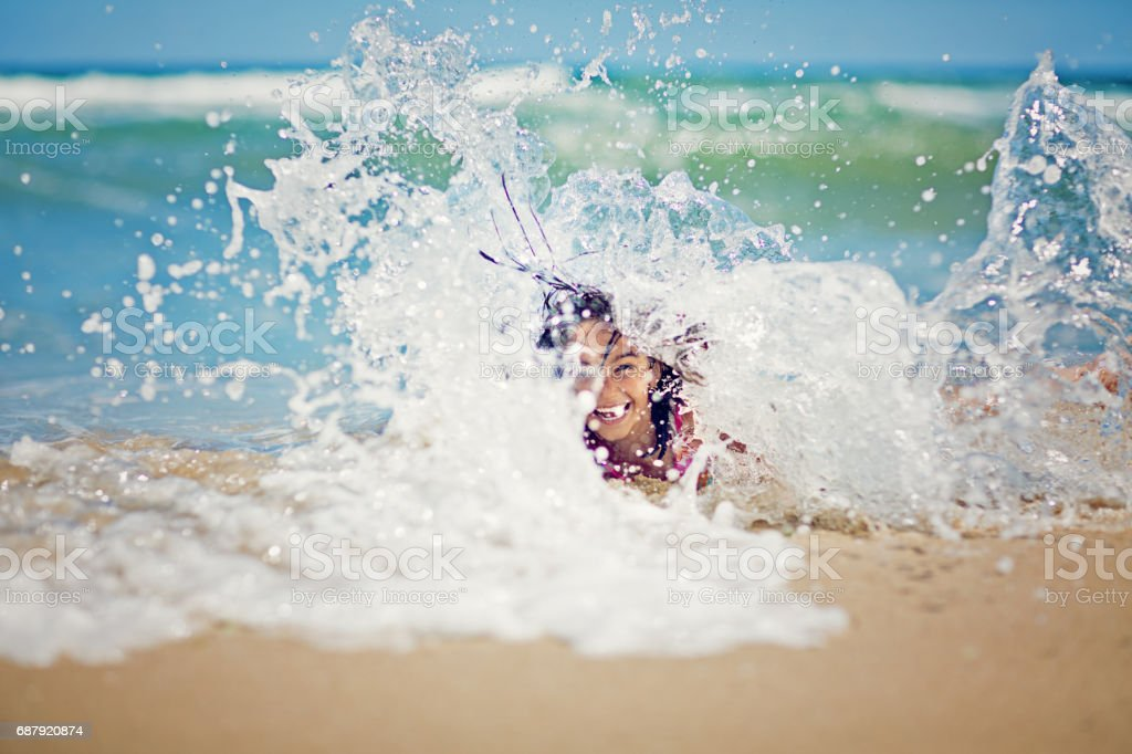 Little girl is playing with the waves on the beach stock photo