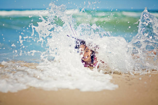Little girl is playing with the waves on the beach – Foto