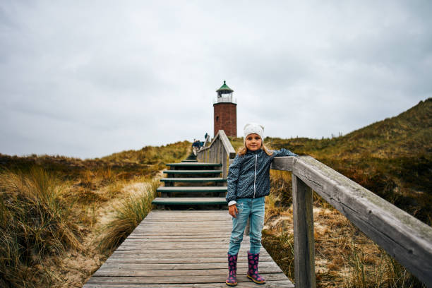 kleines mädchen posiert vor dem leuchtturm - sylt urlaub stock-fotos und bilder