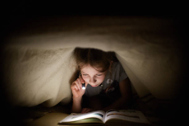 little girl is reading a book under a blanket with a flashlight in a dark room at night stock photo