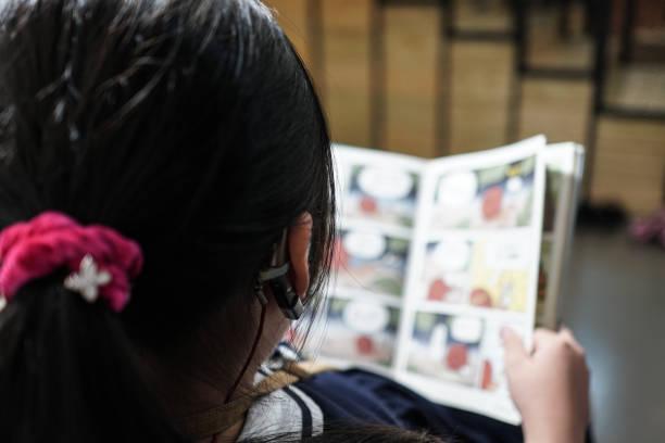 das kleine mädchen liest in der bibliothek. mit einem hörgerät. - comic stock-fotos und bilder