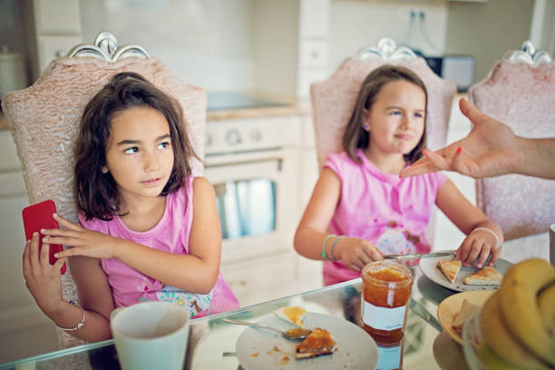little girl is refusing to give mobile phone to her mother at the breakfast - eating technology stock photos and pictures