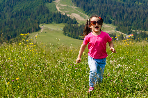 A little girl is running around the mountains