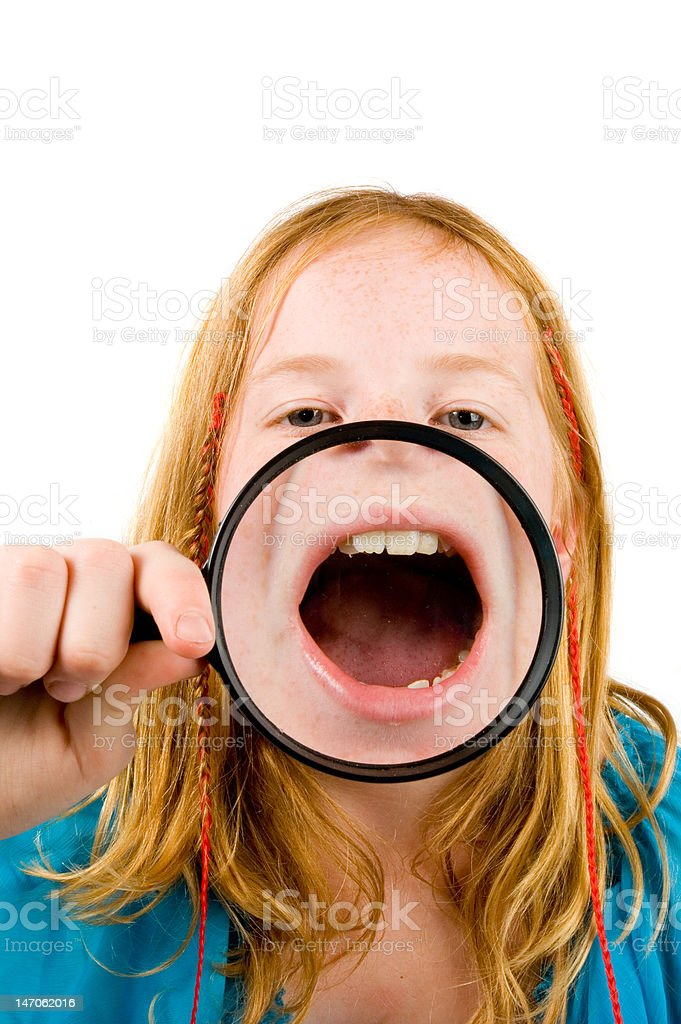 little girl is showing her mouth through a magnifying-glass stock photo