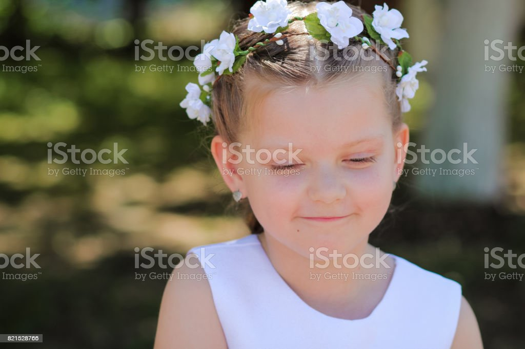 little girl is shy and looks down, a child with a wreath of artificial flowers on her head stock photo