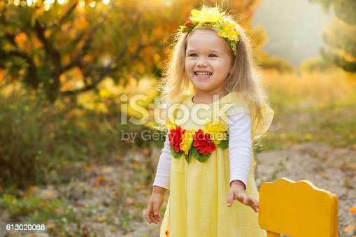 istock Little girl is sitting on chair in autumn garden 613020088