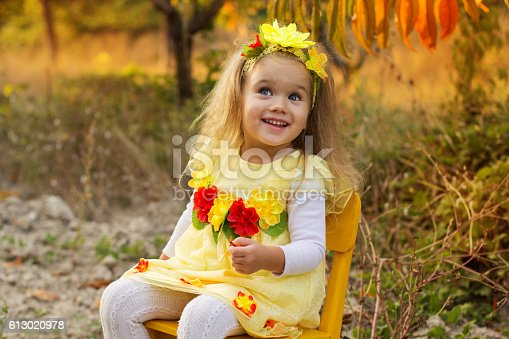 istock Little girl is sitting on chair in autumn garden 613020978