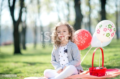 istock Little girl is sitting on green grass near basket with Easter eggs 1139657319
