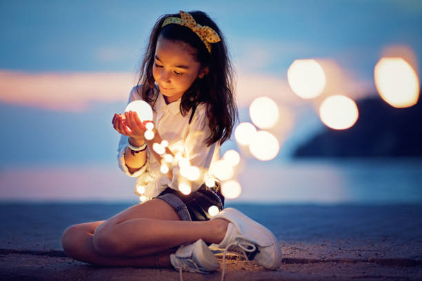 Little girl is sitting on the pier and playing with the mysterious lights stock photo