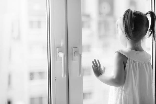A little girl is sitting on the windowsill. A bouquet of flowers - foto stock
