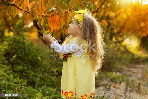 istock Little girl is sitting on yellow chair 613019864