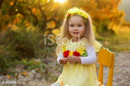 istock Little girl is sitting on yellow chair 613020538