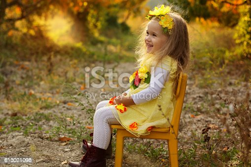 istock Little girl is sitting on yellow chair 613021098