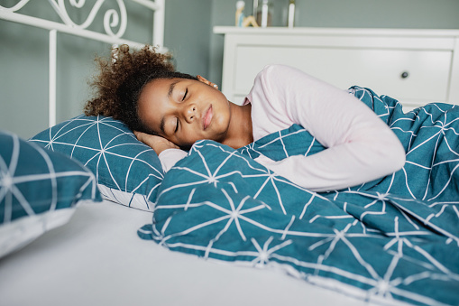 a little African American carefree girl sleeps in bed