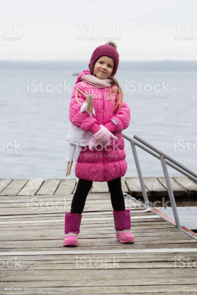 little girl is standing on a river pier. stock photo