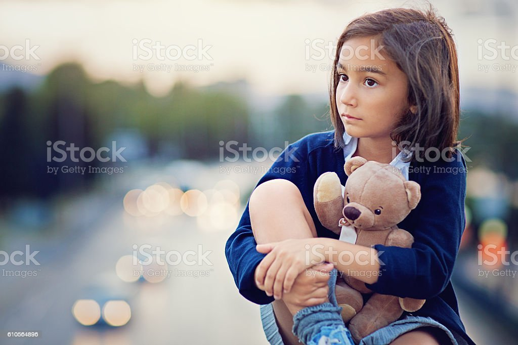 Little girl is standing sad on the bridge stock photo