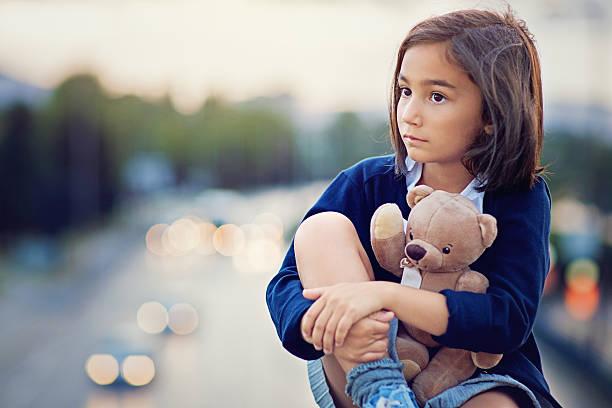 Little girl is standing sad on the bridge - Photo