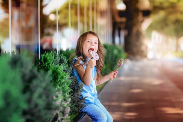 kleines mädchen ist geschmack bonbon am stiel - versuche nicht zu lachen stock-fotos und bilder