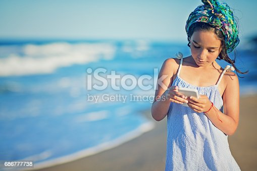 Little girl is texting on the beach
