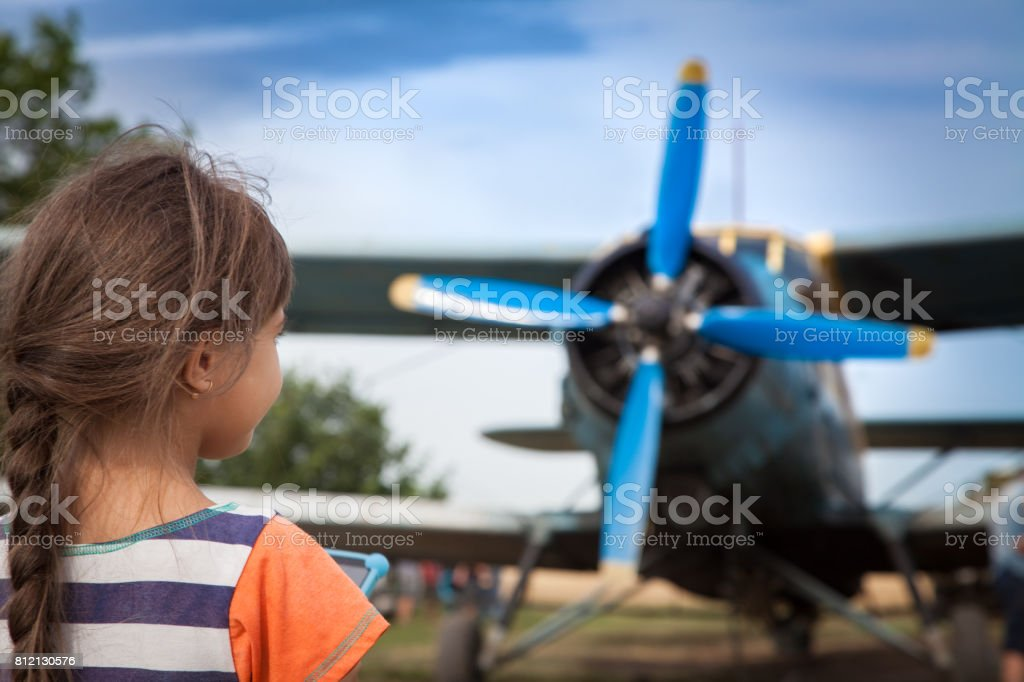 Little girl is watching on an airplane with big propeller stock photo