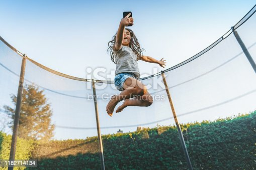 little girl jumping high on trampoline under blue sky while chatting on mobile