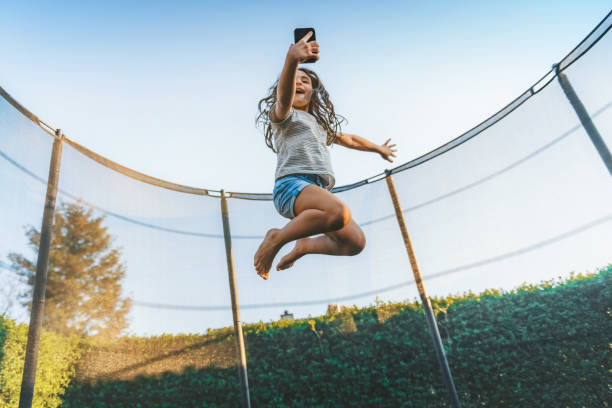 little girl jumping high on trampoline with mobile stock photo