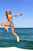 Little girl jumping in the sea. Happy summer day