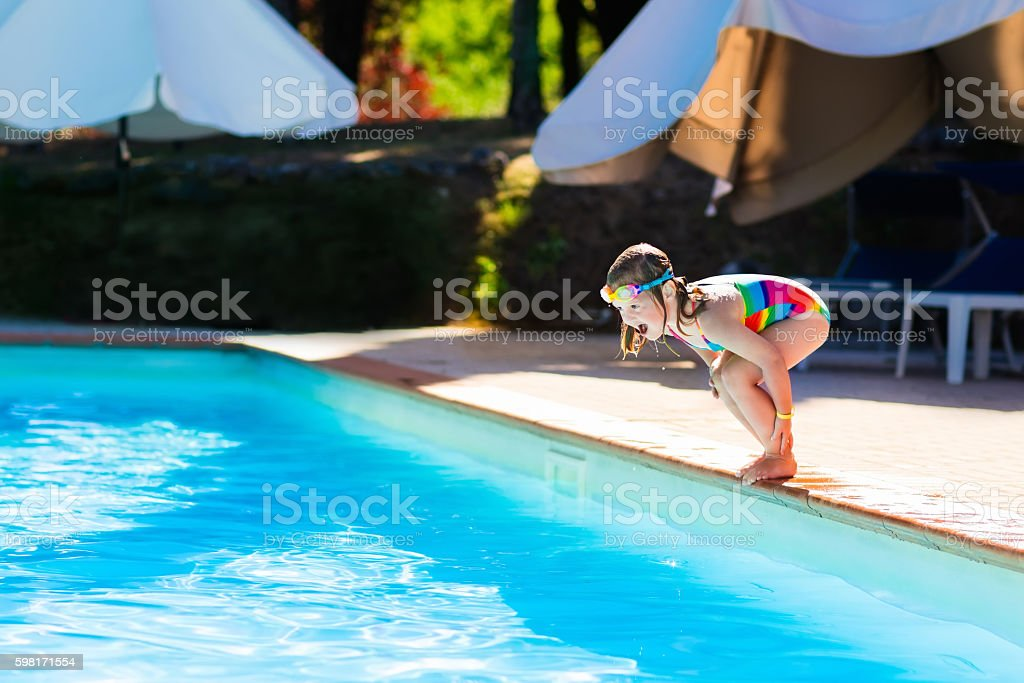 Little girl jumping into outdoor swimming pool stock photo